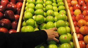 "BEIJING - JANUARY 27:  A shopper chooses granny smith apples at the newly-opened Tesco supermarket on January 27, 2007 in Beijing, China. The UK giant opened its first own-brand supermarket in Beijing after investing in 46 stores across China under the name of its Chinese partner, Le Gou, which translates as ""Happy Shopping"". Tesco's new store in Beijing is competing with other international chains that are well established in China, such as Wal-Mart and Carrefour.  (Photo by Andrew Wong/Getty Images)"